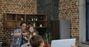 Η μητέρα με το γιο αυξάνει το φορητό προσωπικό υπολογιστή κάνοντας την τηλεοπτική κλήση που παρουσιάζει μαγειρεύοντας γεύμα πατέρ απόθεμα βίντεο