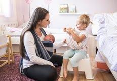 Η μητέρα με το γιο στη σφεντόνα και η μεταφορά κορών teddy αντέχουν Στοκ Εικόνα
