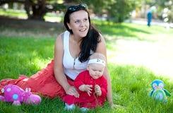 Η μητέρα με το μωρό παίζεται στον πράσινο χορτοτάπητα Στοκ εικόνες με δικαίωμα ελεύθερης χρήσης