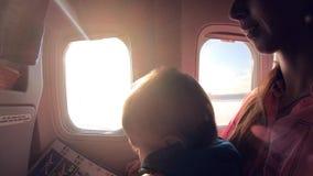 Η μητέρα με το παιδί κάθεται στο αεροπλάνο κοντά στο παράθυρο κατά τη διάρκεια της πτήσης στον ήλιο απόθεμα βίντεο