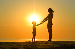 Η μητέρα με το παιδί κάθεται στην παραλία στο ηλιοβασίλεμα Στοκ Εικόνα