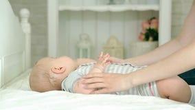 Η μητέρα ντύνει το νήπιο Μια νέα μητέρα και ένα εξάμηνο παιδί Το Mom φορά τις πάνες, τα τζιν και ένα πουκάμισο, κάλτσες Ένα παιδί απόθεμα βίντεο