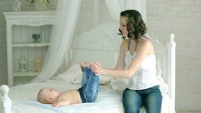 Η μητέρα ντύνει το νήπιο Μια νέα μητέρα και ένα εξάμηνο παιδί Το Mom φορά τις πάνες, τα τζιν και ένα πουκάμισο, κάλτσες Ένα παιδί φιλμ μικρού μήκους