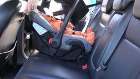 Η μητέρα ξεσφίγγει τις ζώνες ασφάλειας στο παιδί στο κάθισμα αυτοκινήτων 4K απόθεμα βίντεο
