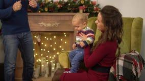 Η μητέρα, ο πατέρας και λίγο μωρό είναι στο δωμάτιο με τη διακόσμηση Χριστουγέννων Άτομο που μιλά με τη σύζυγό του που ενώ απόθεμα βίντεο