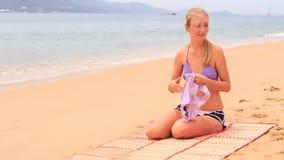 η μητέρα παρουσιάζει μαγιό στη συνεδρίαση κορών στην αμμώδη παραλία απόθεμα βίντεο
