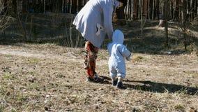 Η μητέρα περπατά με ένα μικρό παιδί και κρατά το χέρι του Οικογενειακή έννοια απόθεμα βίντεο