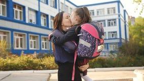 Η μητέρα περπατά με την κόρη της ένα πρώτος-γκρέιντερ στη σχολική στολή και με ένα σακίδιο πλάτης κοντά στο σχολικό κτίριο απόθεμα βίντεο
