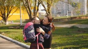 Η μητέρα περπατά το μικρό κορίτσι σε μια σχολική στολή στο σχολείο Μητέρα και κόρη που κρατούν μαζί τα χέρια πηγαίνοντας στο σχολ απόθεμα βίντεο