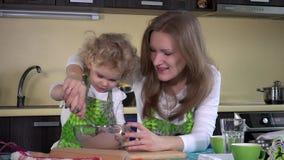 Η μητέρα που διδάσκει τη λατρευτή κόρη της για να συσσωματώσει ψήνει στην κουζίνα απόθεμα βίντεο