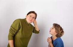 Η μητέρα που κοιλαίνει το χέρι της πίσω από το αυτί μπορεί ` τ να ακούσει το γιο της στοκ φωτογραφία με δικαίωμα ελεύθερης χρήσης