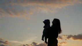 Η μητέρα ρίχνει επάνω στο μωρό στο ηλιοβασίλεμα απόθεμα βίντεο