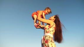 Η μητέρα ρίχνει την κόρη της μέχρι τον ουρανό blu σε αργή κίνηση μαγνητοσκόπηση Παιχνίδια Mom με το μικρό παιδί στα όπλα της ενάν απόθεμα βίντεο