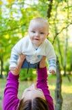 Η μητέρα ρίχνει το ευτυχές μωρό επάνω Στοκ Φωτογραφία