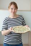 Η μητέρα στο ριγωτό πουκάμισο ναυτικών ` s φέρνει το μεγάλο πιάτο πιτσών και εκμετάλλευσης στα χέρια, πορτρέτο Στοκ Εικόνες