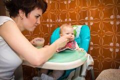 Η μητέρα ταΐζει τον πουρέ μωρών μωρών Στοκ Φωτογραφίες