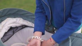 Η μητέρα ταΐζει το γάλα παιδιών μικρών παιδιών αγοράκι από ένα πλαστικό μπουκάλι με μια φωτεινή μπλε θηλή - καυκάσιο λευκό παιδί  απόθεμα βίντεο