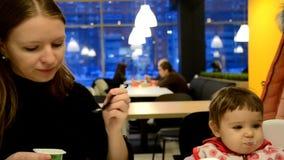 Η μητέρα ταΐζει το μωρό της σε έναν καφέ οικογένεια, τρόφιμα, παιδί, έννοια κατανάλωσης και πατρότητας - μητέρα με τον πουρέ και  απόθεμα βίντεο