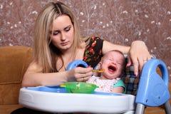 Η μητέρα ταΐζει το παιδί Στοκ Εικόνες