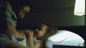 Η μητέρα της Νίκαιας δίνει ένα προηγούμενο φιλί στο παιδί της πρίν πηγαίνει στο κρεβάτι, αγκαλιάζει ήπια το παιδί και την καλύπτε απόθεμα βίντεο