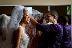 Η μητέρα της νύφης ρυθμίζει το πέπλο Στοκ Φωτογραφία