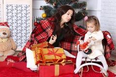 Η μητέρα τυλίγει επάνω την κόρη με ένα καρό Στοκ εικόνες με δικαίωμα ελεύθερης χρήσης