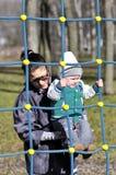 Η μητέρα υποστηρίζει το μωρό στο πλέγμα παιχνιδιών Στοκ εικόνα με δικαίωμα ελεύθερης χρήσης