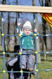 Η μητέρα υποστηρίζει το παιδί στο πλέγμα παιχνιδιών Στοκ φωτογραφίες με δικαίωμα ελεύθερης χρήσης