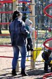 Η μητέρα υποστηρίζει το παιδί στο πλέγμα παιχνιδιών Στοκ Εικόνες