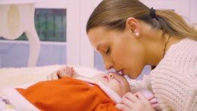 Η μητέρα φιλά ήπια ένα νεογέννητο κοριτσάκι απόθεμα βίντεο