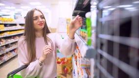 Η μητέρα ψάχνει μόνο τον πουρέ και τους χυμούς φρούτων παιδιών ` s μέσα της αγοράς και σκέφτεται για να αγοράσει Όμορφο όμορφο πρ απόθεμα βίντεο