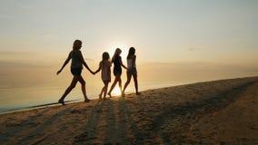 Η μητέρα δύο και η κόρη είναι στην παραλία στο ηλιοβασίλεμα απόθεμα βίντεο