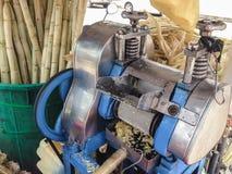 Η μηχανή για κάνει το χυμό ζαχαροκάλαμων με το υπόβαθρο καλάμων ζάχαρης από στοκ εικόνες
