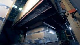 Η μηχανή εργοστασίων ανεβαίνει, σφραγίζοντας τα κιβώτια με τα μπουκάλια σε ένα εργοστάσιο 4K φιλμ μικρού μήκους