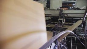 Η μηχανή κάμπτει το χαρτόνι για τα κιβώτια με το λογότυπο στο εργαστήριο απόθεμα βίντεο