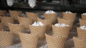 Η μηχανή ρομπότ χύνει αυτόματα το παγωτό σε μια γκοφρέτα κοιλαίνει Οι αυτόματες γραμμές μεταφορέων για την παραγωγή του πάγου φιλμ μικρού μήκους
