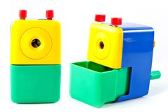Η μηχανική ξύστρα για μολύβια περιστρέφεται με μπλε κιτρινοπράσινο χεριών που απομονώνεται στο άσπρο υπόβαθρο Στοκ φωτογραφίες με δικαίωμα ελεύθερης χρήσης