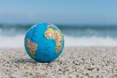 Η μικρή γήινη σφαίρα βρίσκεται σε μια τροπική παραλία Στοκ Εικόνες