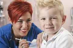 Η μικρή νοσοκόμα αγοριών του δίνει έναν πυροβολισμό Στοκ φωτογραφία με δικαίωμα ελεύθερης χρήσης