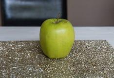 Η μικρή Apple σε έναν χρυσό πίνακα glittery Στοκ Εικόνες