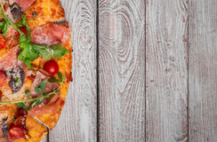 Η μισή από μια πίτσα Πίτσα σε ένα ξύλινο υπόβαθρο Βασιλικός, πράσινα, ζαμπόν και τυρί Cheddar σε μια πίτσα Έννοια Pizzeria διάστη στοκ εικόνα