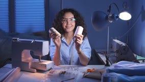 Η μοδίστρα βάζει δύο νήματα στο πρόσωπό της στον εργασιακό χώρο στην εργασία απόθεμα βίντεο
