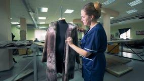 Η μοδίστρα βουρτσίζει ένα παλτό γουνών που κρεμά σε ένα μανεκέν απόθεμα βίντεο
