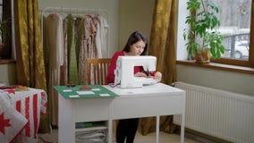 Η μοδίστρα εργάζεται στο ελαφρύ στούντιό της στην ημέρα, κάθεται σε έναν πίνακα και ράβει από τη ράβοντας μηχανή απόθεμα βίντεο