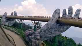Η μοναδική χρυσή γέφυρα με το βάθρο είναι δύο γιγαντιαία χέρια στοκ φωτογραφίες με δικαίωμα ελεύθερης χρήσης