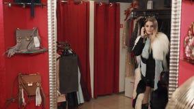 Η μοντέρνη γυναίκα που ντύνεται στα καθιερώνοντα τη μόδα ενδύματα περιστρέφει μπροστά από τον καθρέφτη απόθεμα βίντεο