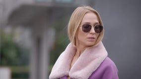 Η μοντέρνη ενήλικη ξανθή γυναίκα διορθώνει τα γυαλιά ηλίου της, που στέκονται υπαίθρια στην ημέρα φθινοπώρου στην πόλη φιλμ μικρού μήκους