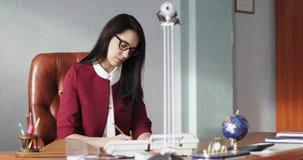 Η μοντέρνη επιχειρησιακή γυναίκα σε ένα ακριβές κοστούμι υπογράφει τα έγγραφα στο γραφείο απόθεμα βίντεο