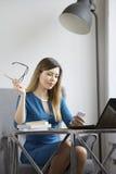 Η μοντέρνη επιχειρησιακή γυναίκα στην αρχή κρατά τα γυαλιά και το κοίταγμα στο smartphone Στοκ εικόνες με δικαίωμα ελεύθερης χρήσης