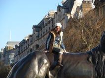 Η μοντέρνη νέα γυναίκα θέτει επάνω στο λιοντάρι χαλκού, Λονδίνο, Αγγλία, UK Στοκ εικόνα με δικαίωμα ελεύθερης χρήσης